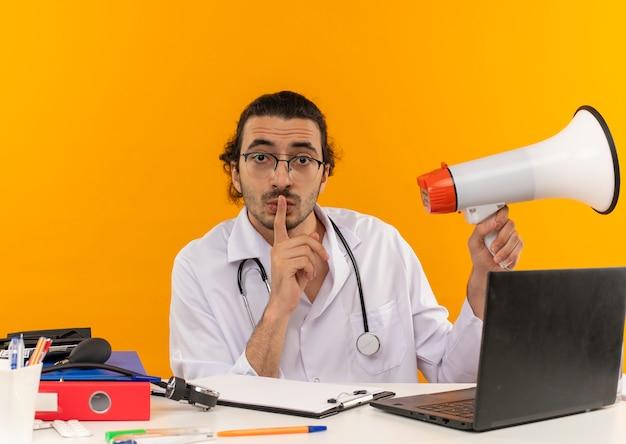 Op zoek naar een jonge mannelijke arts met een medische bril die een medisch gewaad draagt met een stethoscoop die aan het bureau zit?