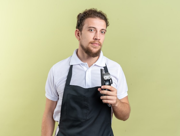 Op zoek naar een jonge mannelijke kapper die een uniform draagt met een tondeuse met kam geïsoleerd op een olijfgroene muur?