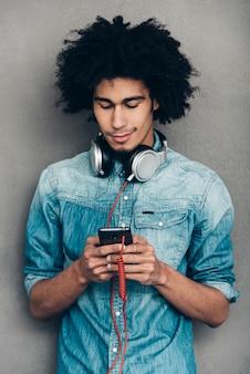 Op zoek naar een nieuw liedje. jonge afrikaanse man die een koptelefoon draagt en zijn smartphone gebruikt