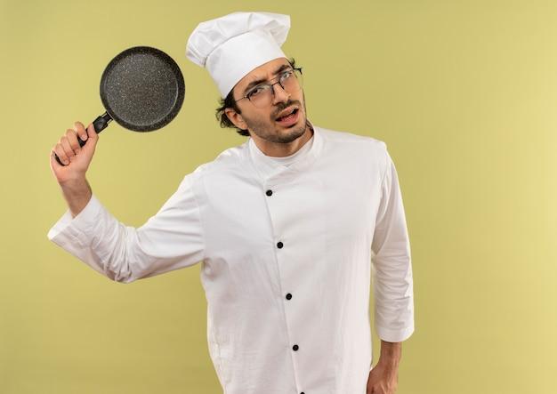 Op zoek naar een onaangename jonge mannelijke kok met een uniform van de chef-kok en een bril die een koekenpan op een groene achtergrond opheft?