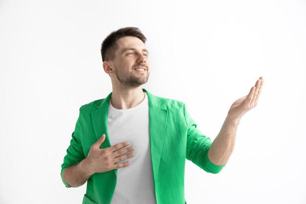 Op zoek naar het beste moment. jonge dromen glimlachende man wacht chanses geïsoleerd op een grijze achtergrond. dromer bij studio in wit t-shirt