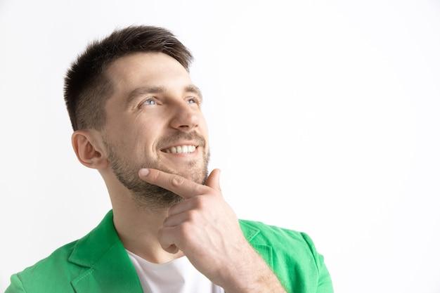 Op zoek naar het beste moment. jonge dromen lachende man wacht chanses geïsoleerd op een grijze achtergrond. dromer bij studio in wit t-shirt