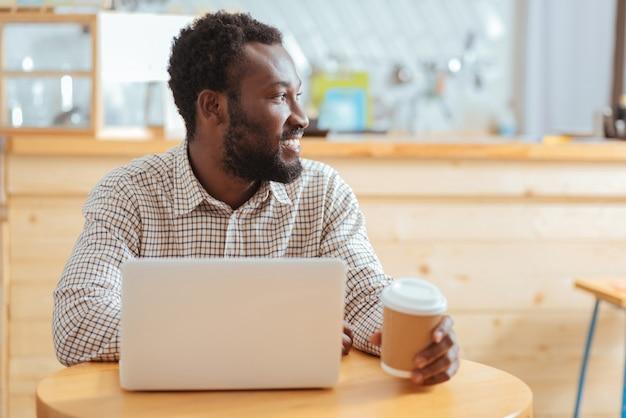 Op zoek naar inspiratie. aangename jonge man zit achter de laptop in een café, houdt een kopje koffie vast en kijkt in de verte alsof hij op zoek is naar inspiratie