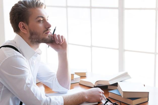 Op zoek naar inspiratie. doordachte jonge man in shirt en bretels die hand op kin houden en wegkijken terwijl hij aan tafel zit met boeken erop