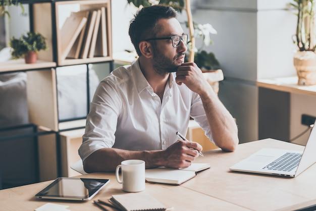 Op zoek naar inspiratie. doordachte volwassen man die een pen vasthoudt en wegkijkt terwijl hij op zijn werkplek op kantoor zit