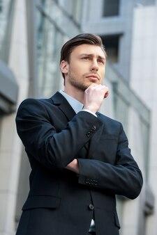 Op zoek naar inspiratie. zijaanzicht van een bedachtzame jongeman in formele kleding die wegkijkt en de hand op de kin houdt terwijl hij buiten staat