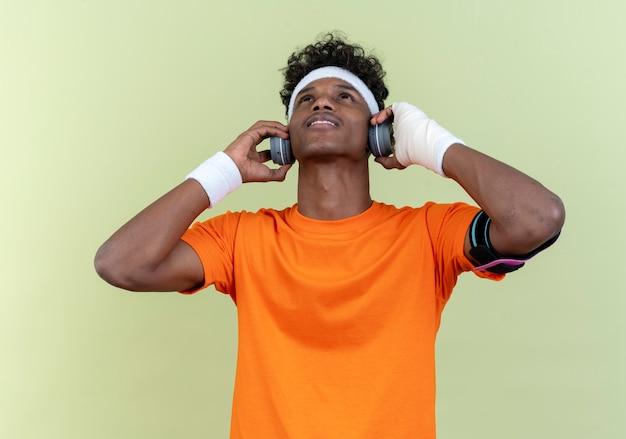 Op zoek naar jonge afro-amerikaanse sportieve man met hoofdband en polsbandje en telefoonarmband met koptelefoon geïsoleerd op groene achtergrond