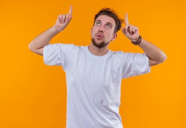 Op zoek naar jonge man met een wit t-shirt wijst naar omhoog op geïsoleerde oranje achtergrond