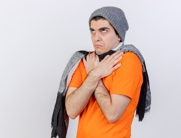 Op zoek naar jonge zieke man met winter hoed met sjaal kruising en hand op schouder zetten