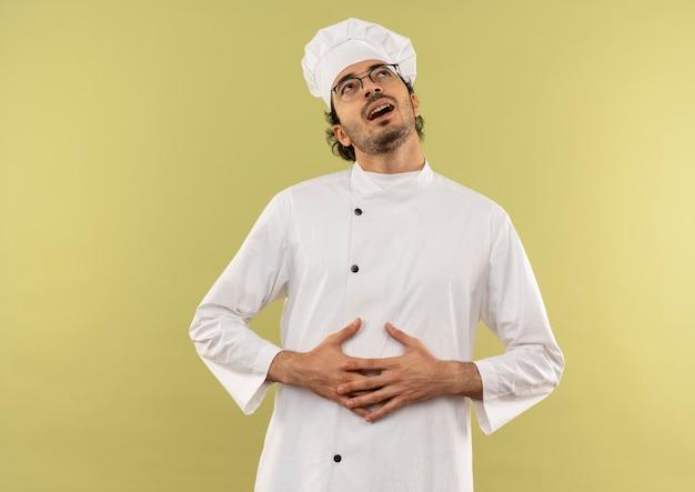 Op zoek naar lachende jonge mannelijke kok met chef-kok uniform en glazen pakte maag
