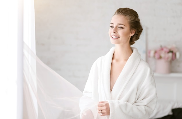 Op zoek naar mijn bruidegom. opgetogen glimlachende jonge bruid die in de witte kamer bij het raam staat en tederheid uitdrukt terwijl ze zich klaarmaakt voor de huwelijksceremonie