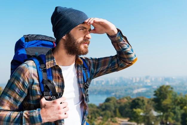 Op zoek naar nieuwe horizonten. knappe jonge man die rugzak draagt en wegkijkt