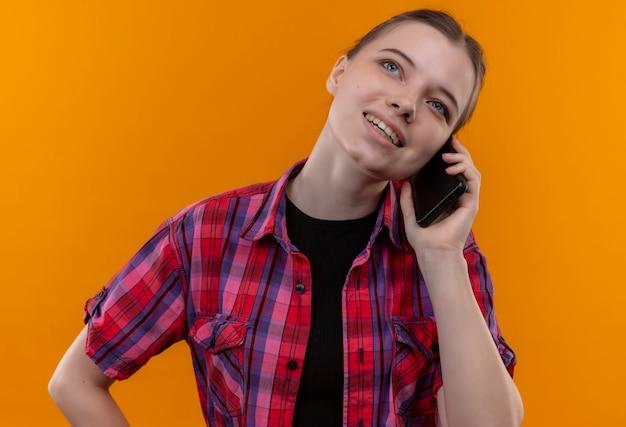 Op zoek naar omhoog jong mooi meisje draagt een rood shirt spreekt over de telefoon op geïsoleerde gele achtergrond