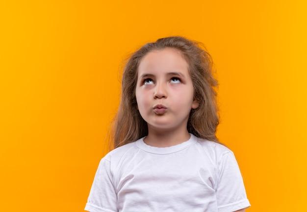 Op zoek naar omhoog klein schoolmeisje met wit t-shirt met kusgebaar op geïsoleerde oranje achtergrond