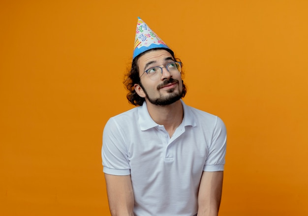 Op zoek naar onder de indruk knappe man met bril en verjaardag glb geïsoleerd op een oranje achtergrond