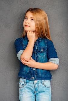 Op zoek naar oplossing. mooi klein meisje houdt hand op kin en kijkt weg terwijl ze tegen een grijze achtergrond staat