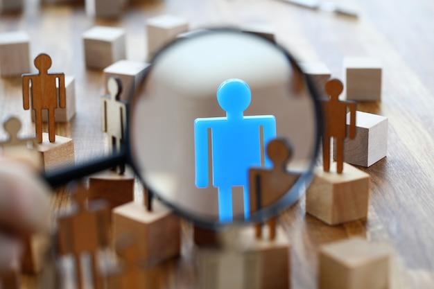 Op zoek naar vermiste persoon in menigte van menselijke speelgoedfiguren met vergrootglas
