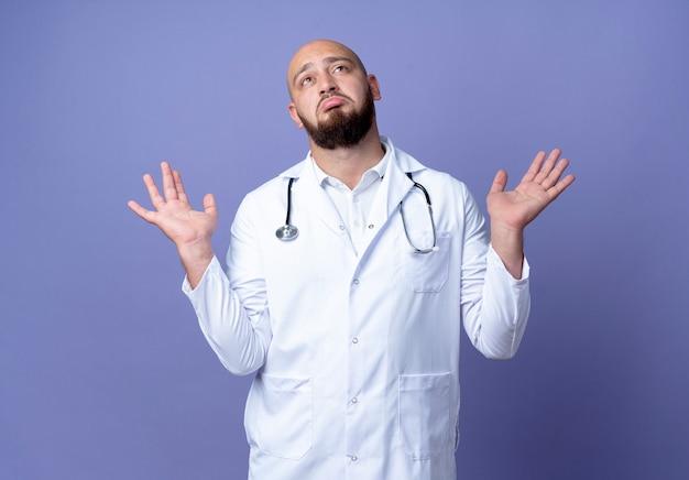 Op zoek naar verwarde jonge kale mannelijke arts die medische mantel draagt en een stethoscoop spreidt handen geïsoleerd op blauwe achtergrond