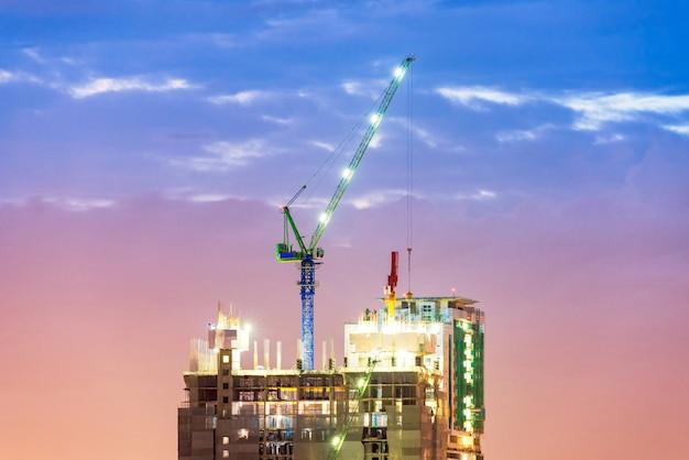 Op zwaar werk berekende industriële kraan bezig werken bij bouwwerf voor nieuwe complexe infrastructuur