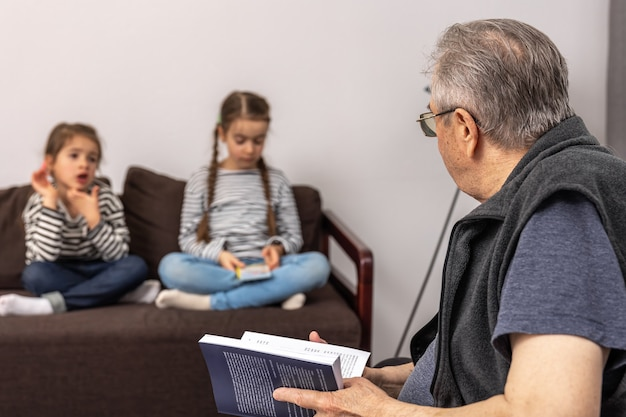 Opa brengt tijd door met zijn kleindochters, leest een boek en vertelt verhalen.