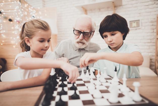 Opa en kinderen spelen schaakstukjes aan boord