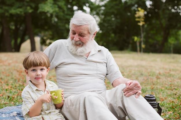 Opa en kleinzoon bij picknick in het park
