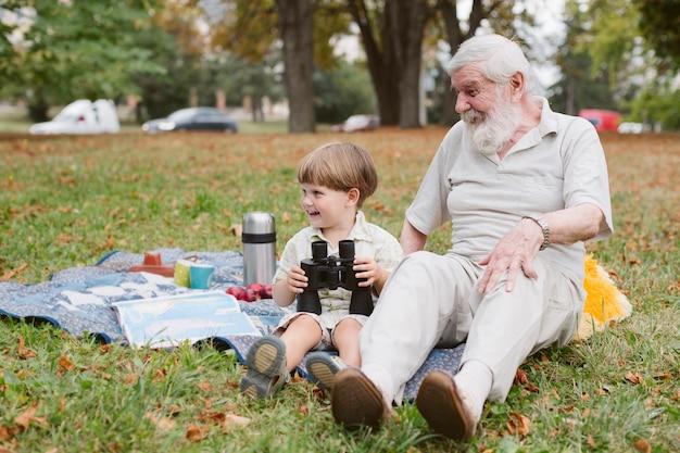 Opa en kleinzoon bij picknick met verrekijker