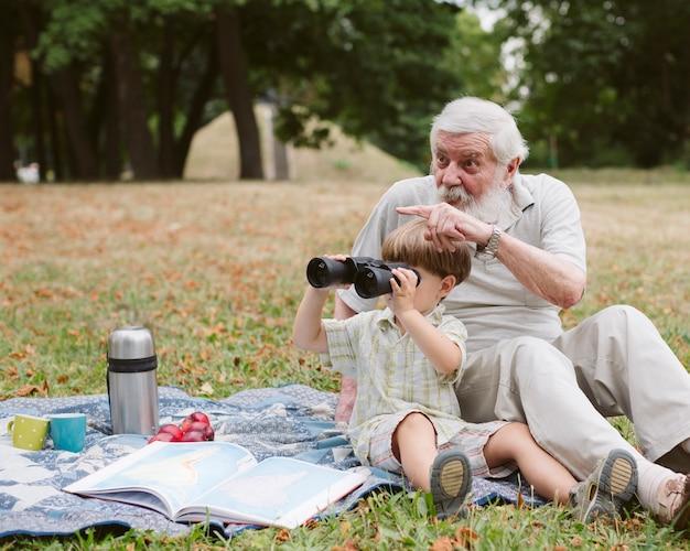 Opa en kleinzoon met verrekijker buiten