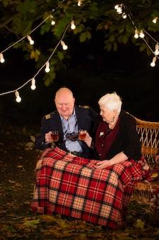 Opa en oma drinken thee in het park.