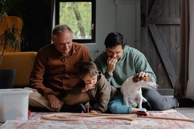Opa en vader spelen thuis met kleinzoon op vloer