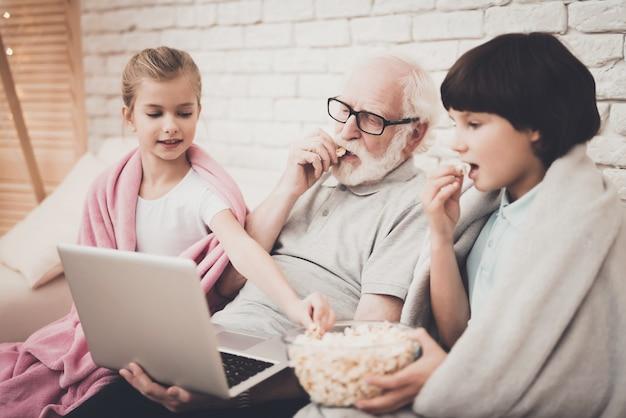 Opa kinderen kijken film op laptop eet popcorn.
