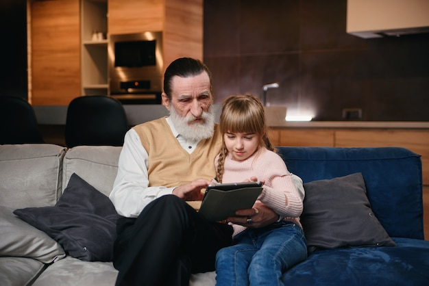 Opa met zijn kleindochter met behulp van tablet pc in gezellige huis. klein meisje leert haar opa om slimme apparaten te gebruiken.