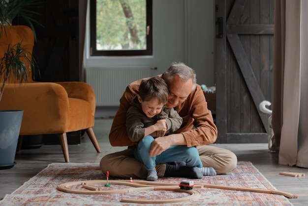 Opa speelt thuis met kleinzoon op vloer