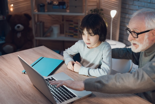 Opa verklaart iets aan kleinzoon met laptop