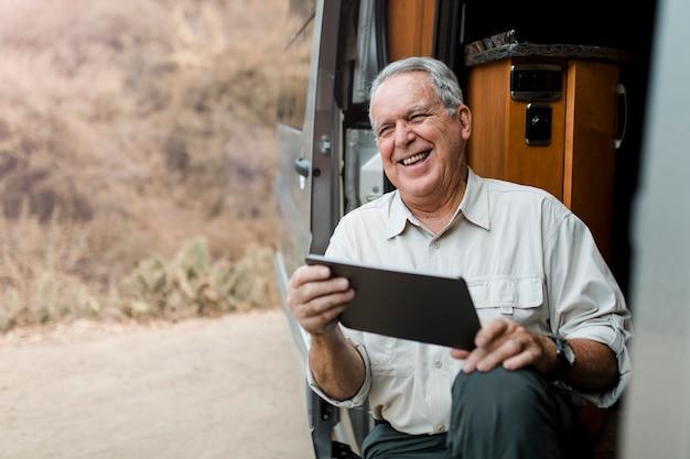 Opa zit in camper terwijl hij naar zijn tablet kijkt