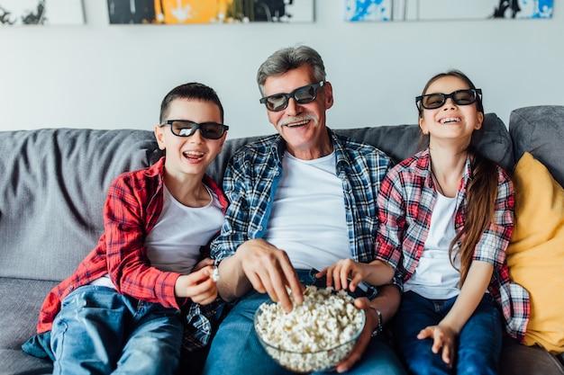 Opa zit met zijn kleinkinderen op de bank in de woonkamer tv te kijken en popcorn te eten