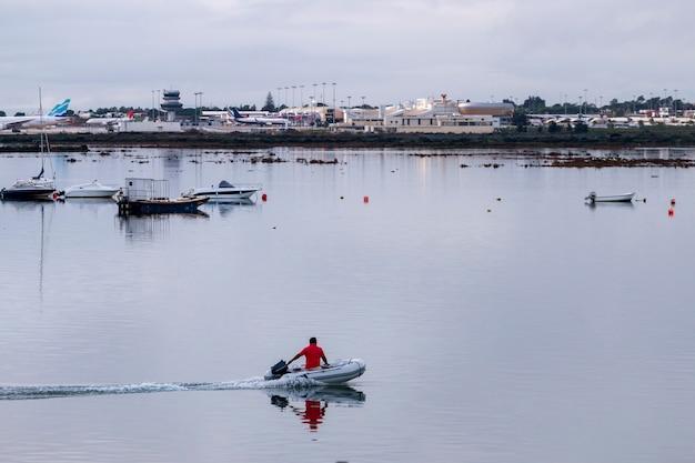 Opblaasbare boot vaart voorbij op de moerassen van ria formosa met overzicht naar de luchthaven van de stad faro, portugal.