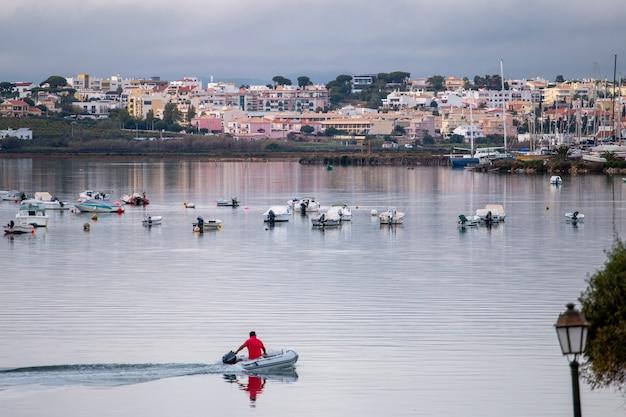 Opblaasbare boot vaart voorbij op ria formosa moerassen met overzicht naar buitenwijken van de stad faro, portugal.