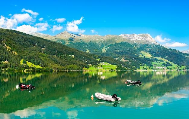 Opblaasbare boten op reschensee, een kunstmatig meer in zuid-tirol, de italiaanse alpen