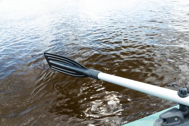Opblaasbare groene boot met peddel. reis- en actief levensstijlconcept.