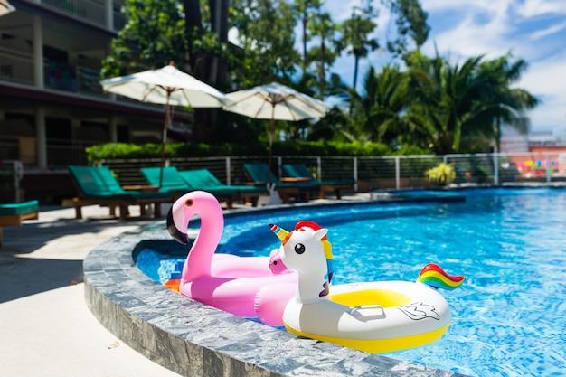 Opblaasbare kleurrijke witte eenhoorn en roze flamingo bij het zwembad.