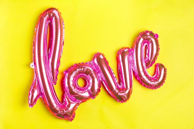 Opblaasbare letters liefde in koraal kleur op gele achtergrond plat lag bovenaanzicht