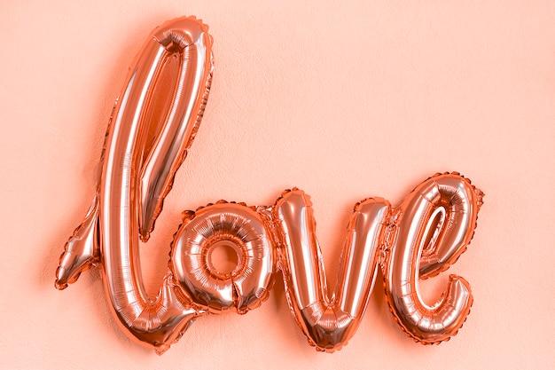 Opblaasbare letters liefde in koraalkleur op roze koraal plat lag