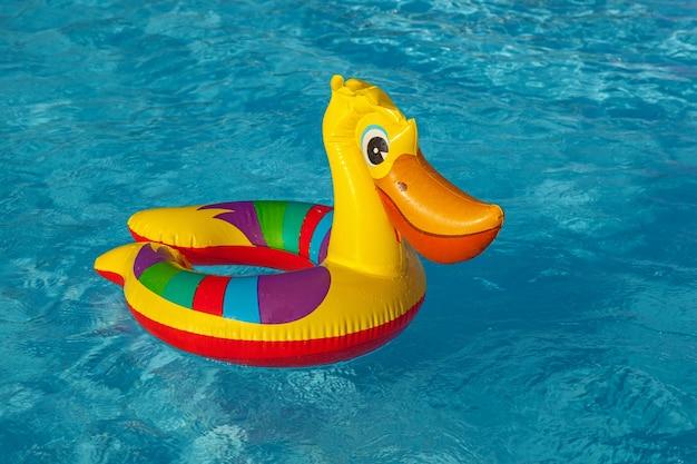 Opblaasbare pelikaan zwemt in het zwembadopblaasbaar speelgoed
