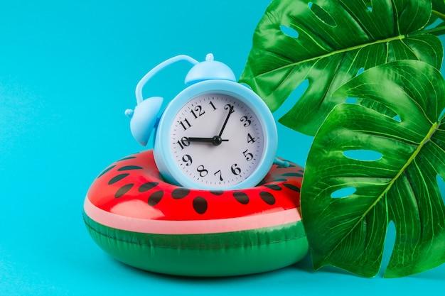 Opblaasbare watermeloen op blauwe achtergrond met monsterabladeren.