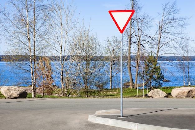 Opbrengst teken op weg naast het blauwe meer