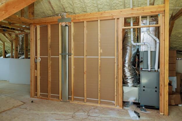 Open ac verwarmingsventilator en buizen in plafond van nieuwe woningbouw.