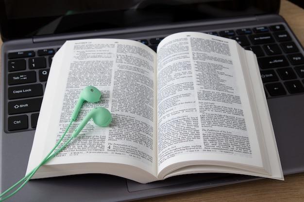 Open bijbel op laptop met hoofdtelefoons.