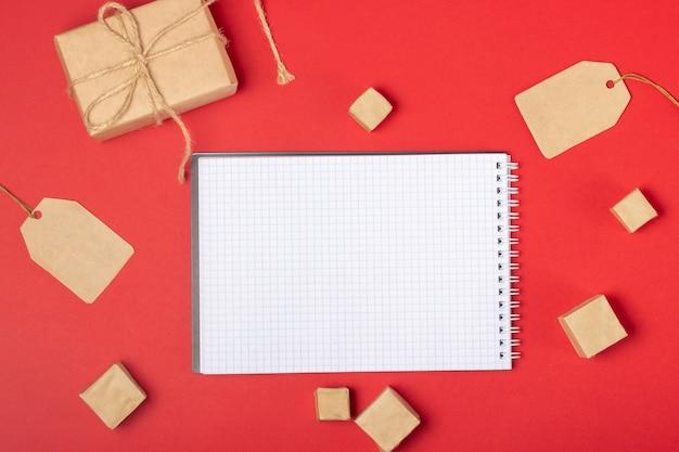 Open blanco notitieboekje met plaats om tekst, winkelwagen en dozen toe te voegen op een felrode achtergrond. online winkelconcept
