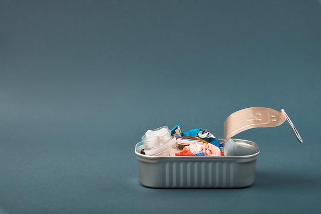 Open blik met plastic afval in plaats van vis erin